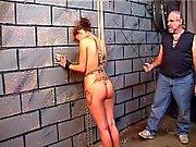 Nicole in bondage gets spanked against brick wall