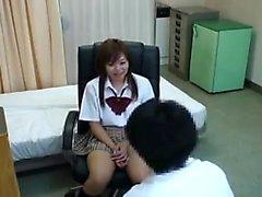 Güzel Japon kız öğrencisi dikkatlice inceleyen bir doktora sahiptir.