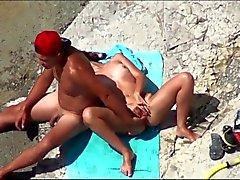 Coppia delle masturbating reciprocamente all'orgasmo ad una spiaggia pubblica