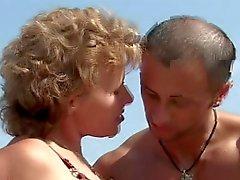 Oudere met kleine tieten grote tepels krijgt neuken op het strand
