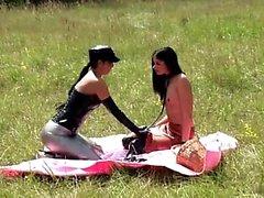 lesbica crespa nei abiti sexy divertire con finto vibratore esterna