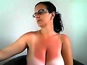 Provoking brunette milf with glasses puts her big hooters o