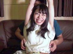 Japanisches nettes Mädchen, das kitzelt