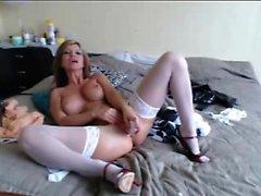 Elegante blonde loira em meias brancas funciona sua buceta em um