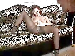 Lusty whore Crissy Moran rubbing her twat with her fingers on the couch