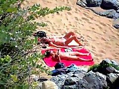 Nude girls on beach sunning .