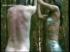 Dirty slave tied to a tree is hit very hard with a whip by horny mistress