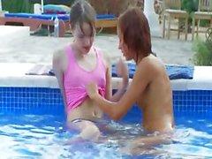 Girlsongirls humides s'embrasser bord de la piscine