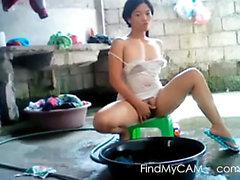 Asiatisk tjej gör tvätt utomhus och retar på webbkamera