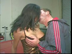 Brunette tranny gets cock sucked & ass fucked by stud on top of car in garage