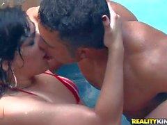 Loupan reçoit la main sur brünett chaude dans le pool
