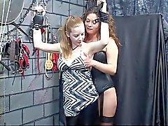 Sex slav blir bunden av läder manschetter och matte ger bröstvårtan tortyr