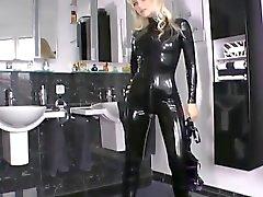 Señora del blonde del negro catsuit de látex brillo atractiva que en su casa