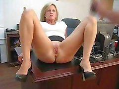 Secrétaire blonde mûr écarte ses cuisses et se masturbe sur le pupitre