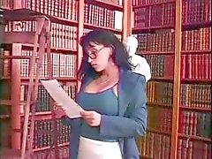 Nuori blondi koulutyttö ja busty brunette kirjastonhoitaja pelatastrapon kirjastossa