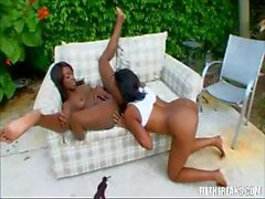 Two ebony lesbians are outside and eat and toy their wet pussies